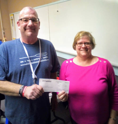 Mercer Savings Bank employee Lori Vian selected Immaculate Conception Youth Group to receive a $200 donation as part of the bank's Mission of Giving. Vian is pictured with Gary Locke.