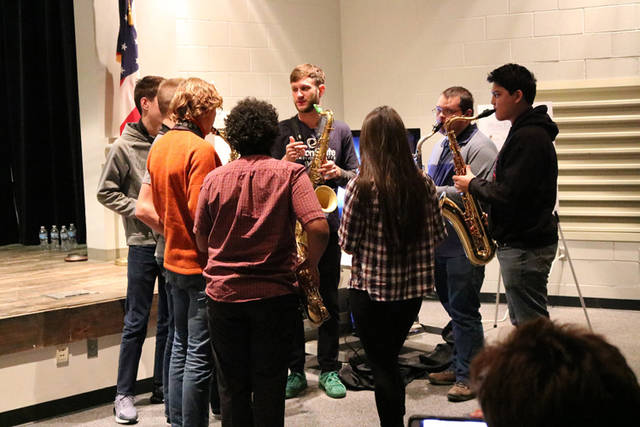 Lucky Chops saxophonist Daro Behroozi gives pointers to local students during a music education clinic held at Edison State Community College.
