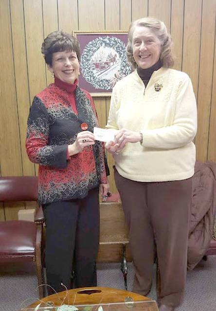 Dianna Wagner, president of the Harry D. Stephens Memorial Trust, presents a check to Lyn Bliss, treasurer of Empowering Darke County Youth.