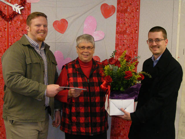Sharon Deeter of Greenville (center) accepts a $50 Darke County Chamber gift certificate from Zac Randall (left) of Randall Insurance Agency for The Daily Advocate's Red Hot Valentine's Day Contest. Holding dozen red roses donated by Helen's Flowers & Gifts is Ben Randall (right) of Randall Insurance Agency.