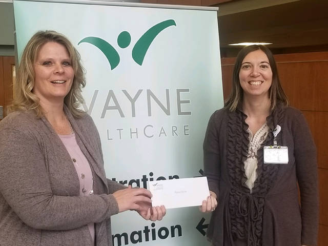 Big Brothers Big Sisters of Shelby & Darke County's Executive Director Jennifer Bruns accepts a check from Lauren Henry, Wilson HealthCare Foundation's director.
