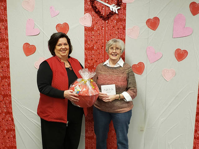 Gloria Harpest (left) representing Greenville National Bank presents Connie Miller of Arcanum a movie night gift basket for The Daily Advocate's Red Hot Valentine's Day Contest. Miller also is holding a $50 gift certificate to Bouser's Barn of Union City, Indiana.