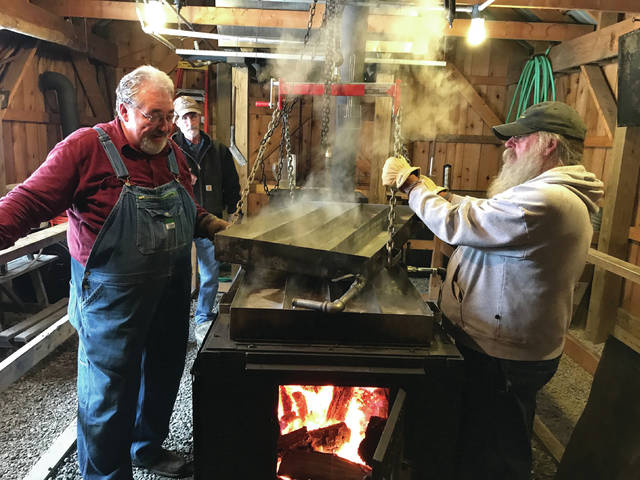 Volunteers use the evaporator to boil sap into syrup.