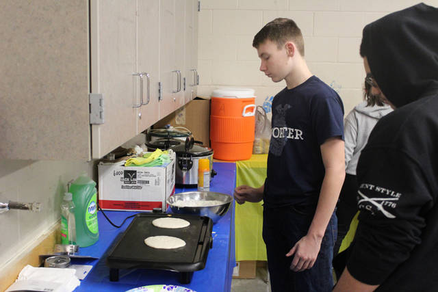 Taven Leach makes pancakes on Feb. 22 during FFA Week for the staff appreciation breakfast.