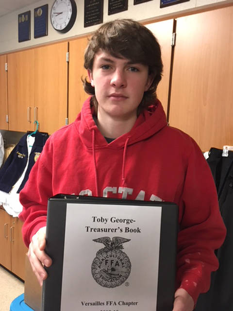 Versailles FFA Treasurer Toby George is shown with his 100 percent Gold Rated Treasurer's book that he submitted to the state.