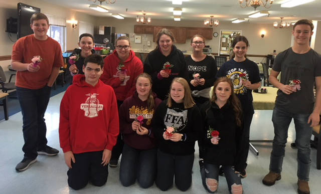 Versailles FFA members are shown with the Valentine Day corsages created by the residents of the nursing home. Pictured are (back, row l-r) Isaiah Hess, Lexie Demange, Laura Wuebker, Haley Smith, Asheleigh Shimp, Abby Petitjean, Franklin Shimp, (front row, l-r) Zach Watren, Breanna Nieport, Paige Gasson Ashleigh Shimp and Kylee Hainline.