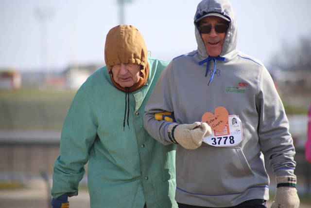 Al Groth, a volunteer, current board member and past board president for State of the Heart Care, helps Harry Fetter walk in State of the Heart's Heart and Sole 5K.