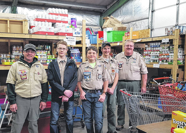 "Area Boy Scouts will be ""Scouting for Food"" to help feed those in need. Pickup begins at 9 a.m. Mar. 16. Show at last year's event are Rick Normile, Mason Garber, Graham Milligan, James Normile and Ken Livingston."