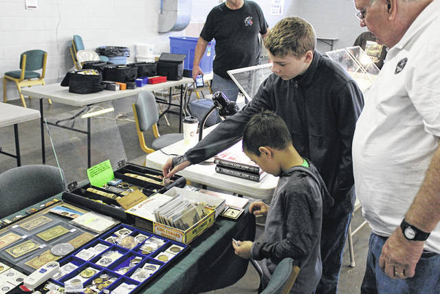 Young hobbyists examine collectibles at the Darke County Coin Club's 53rd annual coin show, held Sunday in Greenville.