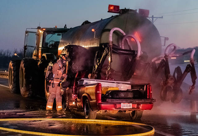 A red Chevy S10 collided into the rear of farm machinery, causing the vehicle to become pinned under the equipment.