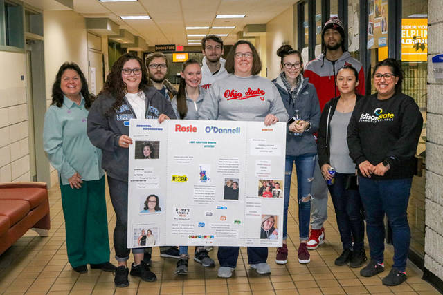Students in April Schmidlapp's class stand with a poster that was created as part of the Women's History Month poster sessions.