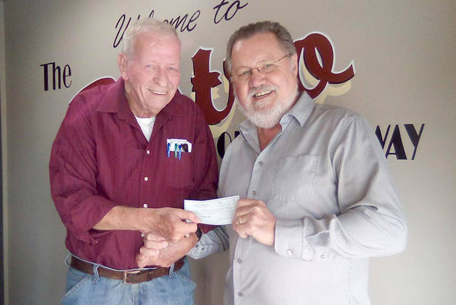 Bob Robinson (left), executive director of Empowering Darke County Youth, accepts a donation from Ted Abney, owner of Bistro Off Broadway.
