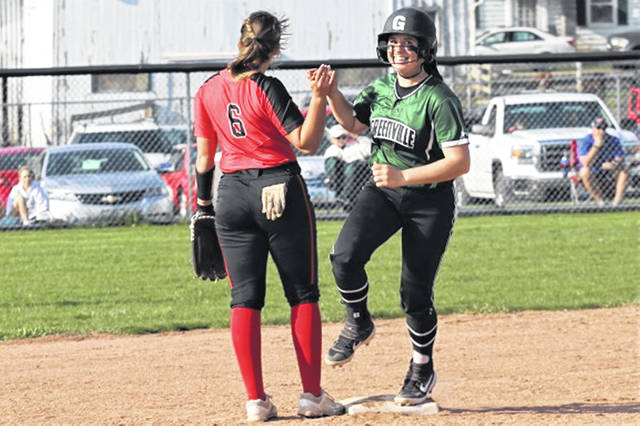 <strong>Susi Blocher gets a high five from Tippecanoe's Brooke Aselage while rounding second following a solo home run to give the Lady Wave a 10-0 lead over the Tippecanoe Lady Red Devils.</strong>