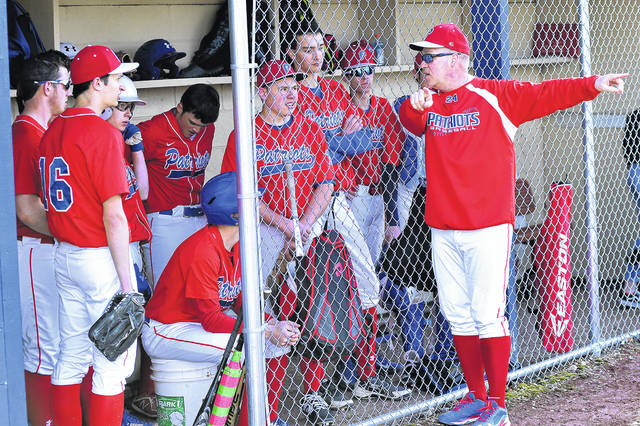 Tri-Village Patriots baseball coach Jim Maples gives instructions to his players in team's win over the Bethel Bees.