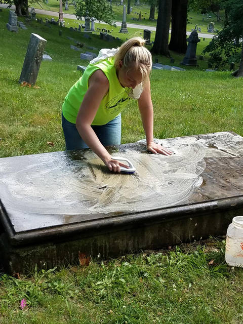 Misti Spillman cleans the ledger monument of Major David Ziegler, a Revolutionary War soldier and the first mayor of Cincinnati.