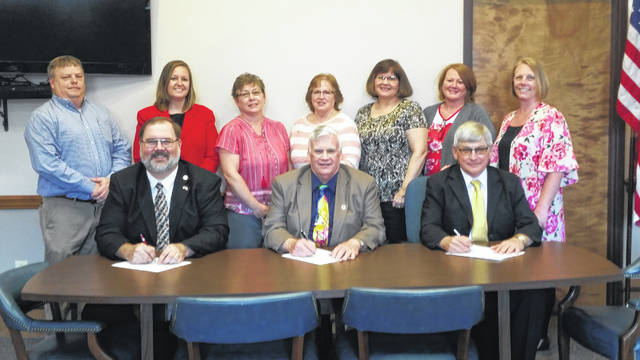 Darke County Commissioners on Wednesday signed a proclamation declaring May 6-10 as In-Demand Jobs Week. Above, front row, left to right are Commissioners Matt Aultman, Mike Stegall and Mike Rhoades. Back row, left to right, are Darke County Ohio Means Jobs personnel Mike Burkholder, Tiffany Thomas, Rhonda Rexrode, Joyce Swisher, Lisa Headley, Sherry Pearson, and Sarah Brubaker. Not pictured is Kathy Stryker.