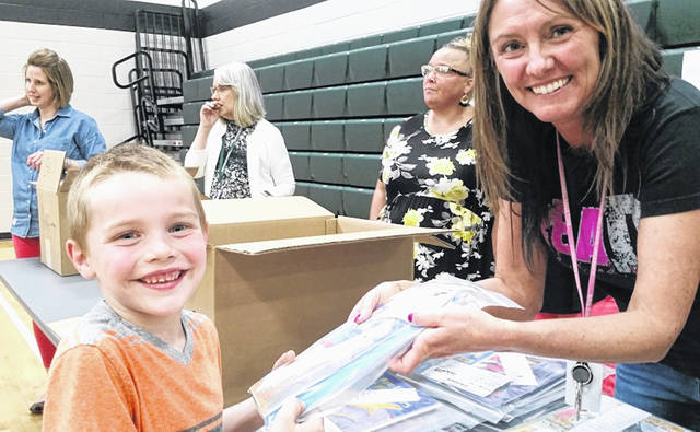 Trevor Singer, 6, receives his first packet of books to read during Greenville Elementary's Summer Reading Program Kickoff on Tuesday.