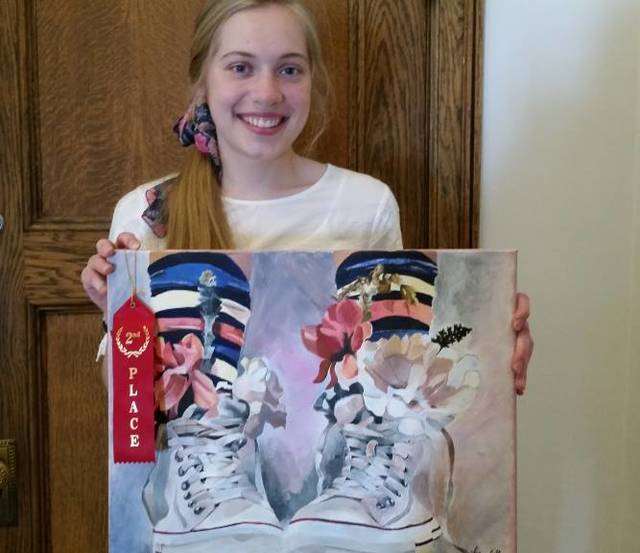 GHS Senior Marabelle Lance holds her painting, Blooms 'n Chucks, which was selected by the Greenville School Board to hang in the Anna Bier Gallery at Memorial Hall.