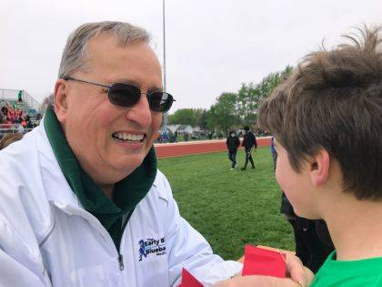 Keith Foutz, publisher of The Early Bird/Daily Advocate is presenting a red ribbon to Jensen Harding, Greenville Middle School student, following the 4 x 100 Traditional relay.