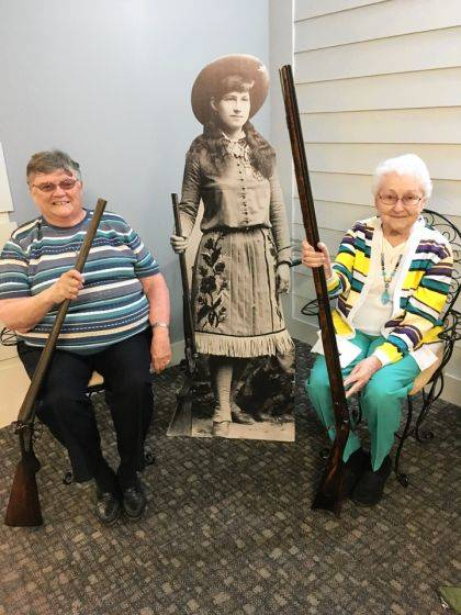 Pat Lemmer (left) and Marilyn Robbins (right) showing sharpshooter Annie the guns that will be at the upcoming Garst Gala.