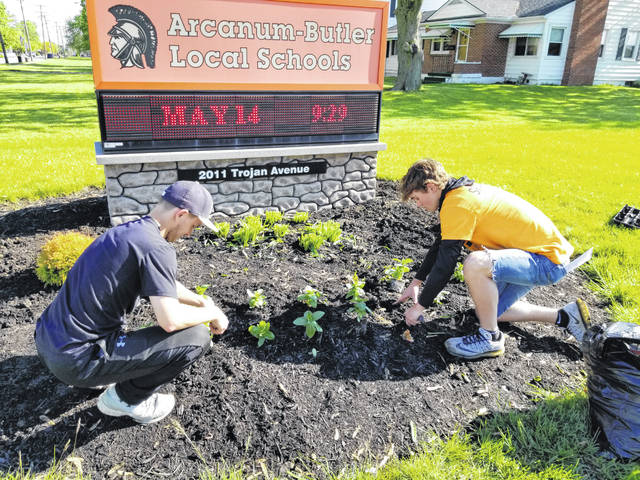Arcanum High School seniors, Michael Fecker and Wade Meeks, plant flowers at the school sign during Serve Arcanum on Tuesday morning. Every year, high school students volunteer to serve the community via a host of projects. Some projects include landscaping while others may be painting or building, all to make a difference within the community.