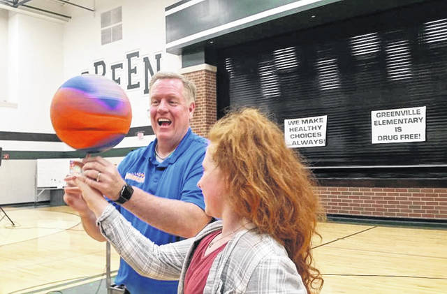 "During a Red Ribbon Week assembly on Thursday, fourth-grader Addi Parin spins a basketball with help from Jim ""Basketball"" Jones."