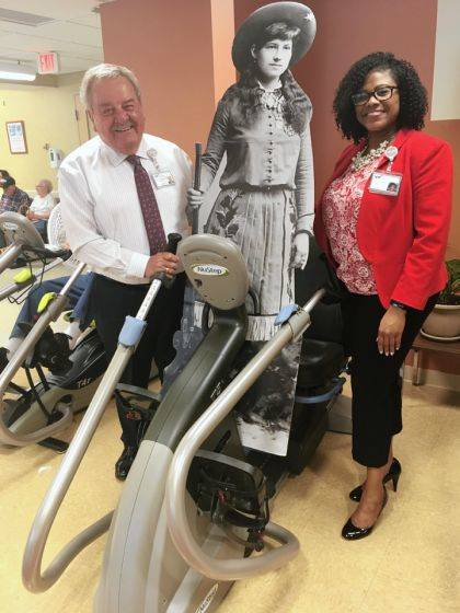 Wayne Deschambeau (left), president and CEO of Wayne HealthCare, and Terri Flood (right), director of marketing and communications, supervise Annie on an exercise machine in the Wayne HealthCare Lifestyle Enhancement Center.