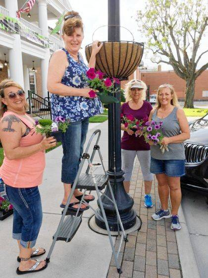 "<p class=""body"">GREENVILLE – Ladybug Garden Club members recently planted the Greenville Traffic Circle with four large containers of Cordyline 'Exotica' with 'Bordeaux' and 'Royal Magenta' Supertunia petunias. Alternanthera 'True Yellow' was added to the planting. The hay racks hold the Bordeaux and Royal Magenta petunias. Planting the hay racks were Sherri Jones, Angela Beumer, Becky Collins, Kim Cromwell and Cathy Detrick. Planting the fountain area was Irma Heiser, Dawn Hissong, Lisa Marcum, Cindy McCallister and Charlene Thornhill."