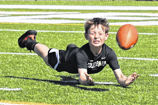 A young Greenville football camper makes a diving catch at the Green Wave's youth football camp.