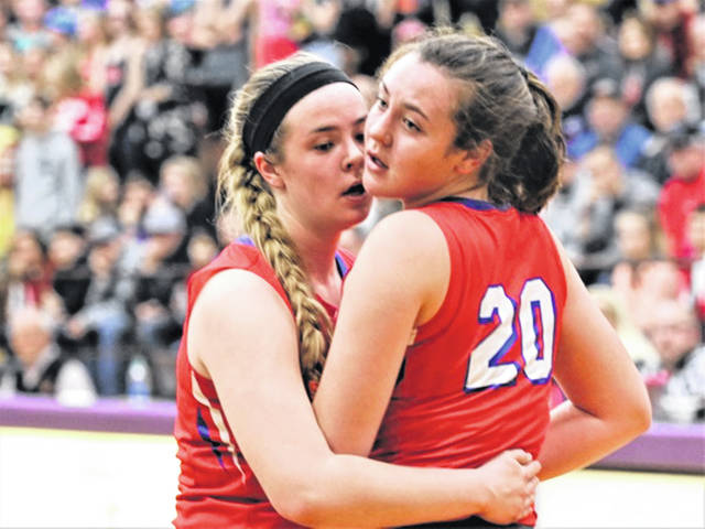 Tri-Village Sisters, Maddie and Meghan (20) Downing meet at the free throw line in the Lady Patriots 2018-19 tournament game against the OHSAA State Champion Minster Lady Wildcats.