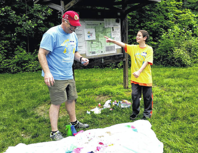 Darke County ESC's multiple disabilities supervisor Bill Nellis, left, and Bradford fourth-grader Hunter Gaines wait for an Alka-Seltzer filled paint canister to explode during Monday's Camp LINK at Chenoweth Trails.