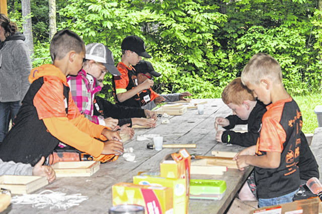 Bethany J. Royer-DeLong | Darke County Media The weather was no problem for the 150 second-grade to fifth-grade students attending the first ever Conservation Day Camp hosted by the Darke County Soil and Water Conservation District (Darke SWCD) at Chenoweth Trails Thursday. Campers enjoyed making bird feeders (pictured), learning about trees, archery, pollinators and more.