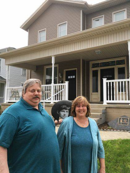 Annie is looking over the shoulder of Mike & Sherri Jones in front of 227 E. Third Street, which they renovated. The stone marker in the background notes that this was the final residence of Annie Oakley.