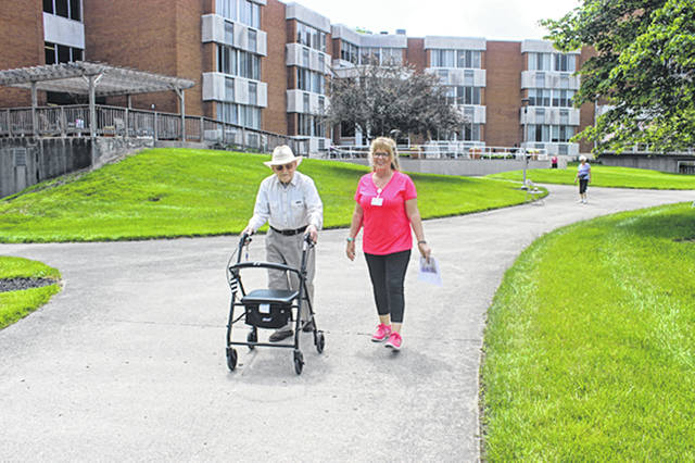 Bethany J. Royer-DeLong|Darke County Media Brethren Retirement Community resident Bob Boyd and Karyl Woolery, BRC Assisted Living Activities Coordinator, walk a lap around the BRC pond in support of The Longest Day Alzheimer's Association fundraising event on Wednesday. The daylong event, inspired by the longest day of summer, included several entertainment venues from Mandy Rismiller to Noah Back, a fundraising pie-in-the-face, food trucks, a butterfly release, and the closing ceremony including the lighting of 65 luminaries.	All proceeds from The Longest Day benefit the Alzheimer's Association, Miami County.
