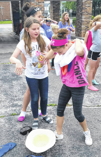 Working together during a summer-themed relay race are We Are the Majority campers and Greenville students Ivy Sommer, left and Kara Blumenstock. The campers had to get dressed in an extra large T-shirt, summer hat, size 13 flip flops, sunglasses and leis before running the relay course.