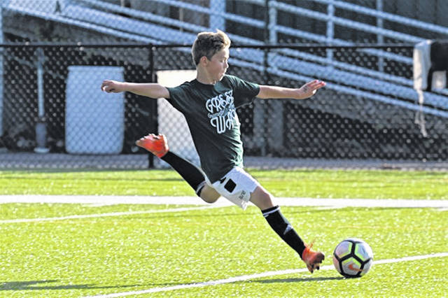 A Greenville Middle School soccer player plays in the teams soccer match against the varsity team to close out of week of boys soccer camp.