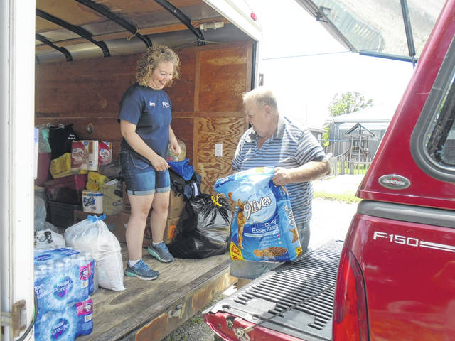 """Mike """"Grumpy""""Wagner of Greenville dropped off some pet food at the Shockney Electric truck at Aukerman's Auto and Tire to be sent to the Vandalia Butler Food Pantry to be disbursed to those affected by the recent tornadic storms. Also shown is Amy Stump, who helped organize the collection project at her father's establishment."""