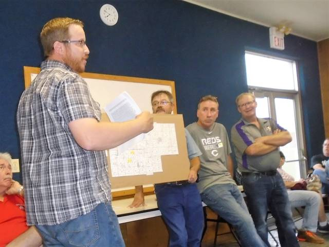 Joe Schmitmeyer, left, holds up a map for the audience to see. Also shown are the Allen Township trustees, from left to right, Mike Bulcher, Chris Mestemaker and Neal Siefring. This took place Thursday night in New Weston.