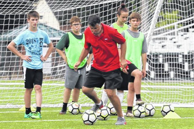 Former professional soccer player Marcel Matis demonstrates a soccer move to Greenville campers at the school's 2019 soccer camp.