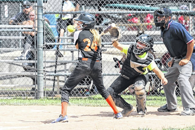 An Arcanum batter gets out of the way of a high-inside pitch at the weekend Cross County League girls softball tournament in Greenville.