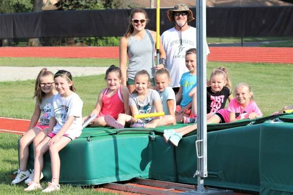 Ohio's all-time best high school girl's pole vaulter and incoming Greenville senior, Riley Hunt takes time to help at the Greenville Track & Field camp. Hunt and Coach Plessinger share a moment with several young campers at the school's pole vault pit.