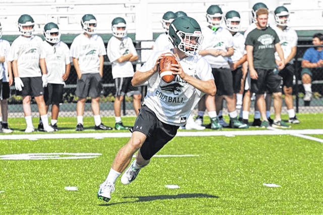 Greenville quarterback Tyler Beyke rolls out completing a touchdown pass to John Butsch against St. Henry in 7-on-7 scrimmage play.