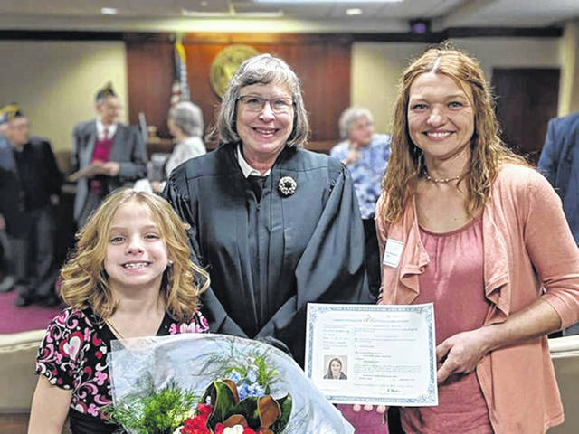 "Courtesy Photo Pictured is Magdalena ""Maggie"" Bradford (along with her daughter, Katarzyna ""Katie"") receiving her Certificate of Naturalization after taking the Oath of Allegiance. Taking the oath completes the process of becoming a U.S. citizen, a moment Bradford states was one of the proudest of her life."