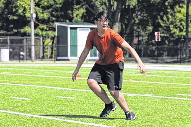 A Greenville junior high camper looks for a pass at the school's football camp.