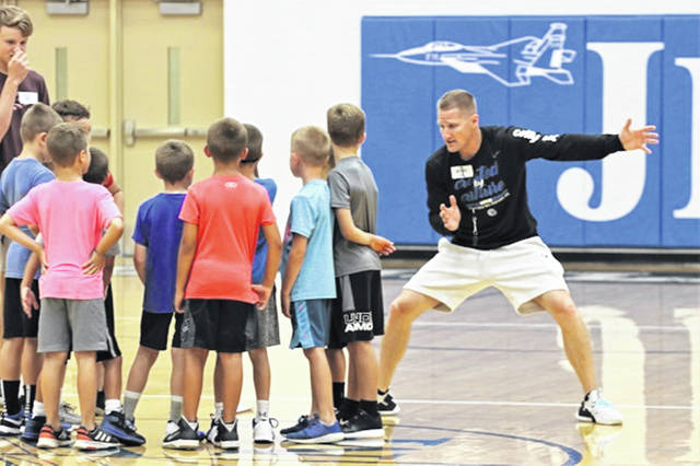 FH head boys basketball coach Troy Meyers demenstrates defensive moves to young campers at the youth basketball camp.