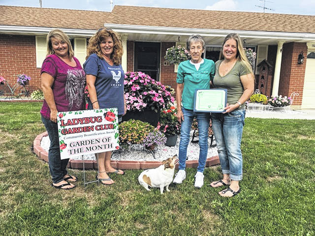 Shown presenting the Residential Landscaping Award are Ladybug members Sherri Jones, Angela Beumer, recipient Robin Magoteax and her dog Maddie Marie, and Ladybug Lisa Marcum.