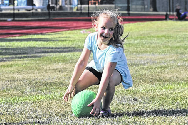 A young Greenville track and field camper catches a ball in game of kickball.