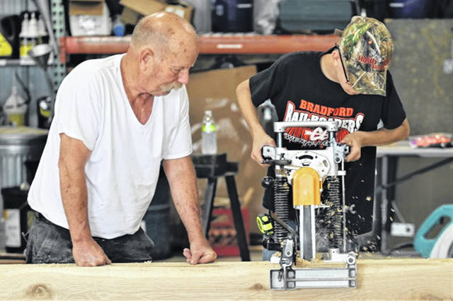 A timber frame instructor watches as a camper uses power equipment at the Light Foundation camp.