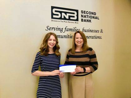 Joy Greer, vice president and retail banking administrator, presents the donation to Crysta Hutchinson Bloomingdale, executive director of Main Street Greenville.