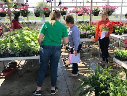 Greenhouse Manager Mallory York is shown helping customers as part of the greenhouse open house.